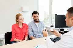 Doctor showing medicine to family couple at clinic Royalty Free Stock Photography