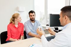 Doctor showing medicine to family couple at clinic Royalty Free Stock Images