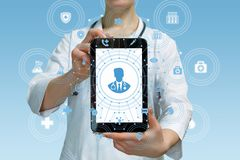A doctor showing a mobile screen with online consultation symbol. A closeup of a doctor showing a mobile screen with a medical worker figure image and a total royalty free stock photo