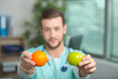 Doctor showing pear and apple. Doctor showing a pear and an apple Stock Photo