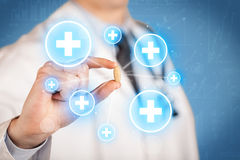 A doctor showing a pill with crosses Royalty Free Stock Photos