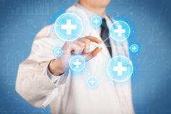 A doctor showing a pill with crosses Royalty Free Stock Images