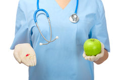 Doctor showing pill and green apple. Isolated Stock Images