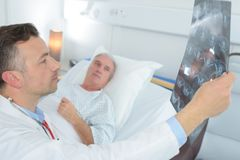 Doctor showing radiologist result to patient stock photography