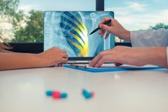 Doctor showing a x-ray of chest with pain on the ribs on a laptop to a woman patient. Pills on the desk. Doctor showing a x-ray of chest with pain on the ribs on royalty free stock photo
