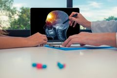 Doctor showing a x-ray of skull with pain in the front of the brain on a laptop to a woman patient. Headache migraine concept. Doctor showing a x-ray of skull stock image