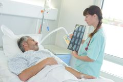 Doctor showing x-ray to patient on bed. A doctor showing an x-ray to a patient on bed Royalty Free Stock Image