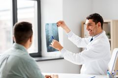 Doctor showing x-ray to patient at hospital. Medicine, healthcare and people concept - smiling doctor showing x-ray to patient at medical office in hospital royalty free stock images