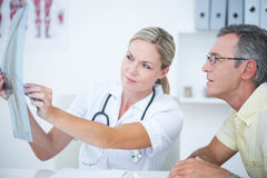 Doctor showing X rays to her patient Stock Image