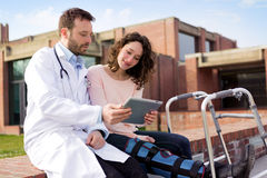 Doctor showing reeducation's tips on tablet Stock Images