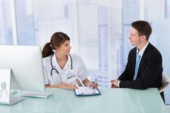 Doctor showing report to businessman in clinic Stock Image