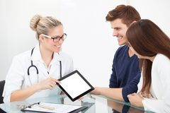 Doctor showing report to couple on digital tablet Stock Photo