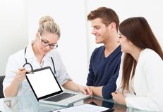 Doctor showing report to couple on laptop. Female doctor showing medical report to couple on laptop at clinic Stock Photo