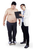 Doctor showing report to fat man Royalty Free Stock Photo
