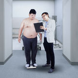 Doctor showing report to a fat patient Stock Image