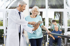 Doctor Showing Reports On Computer To Woman In Fitness Center Stock Images
