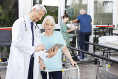 Doctor Showing Reports On Digital Tablet To Woman Using Walker. Mature male doctor showing reports on digital tablet to senior women using walker at fitness Stock Images