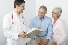 Doctor Showing Reports To A Senior Couple Stock Photography