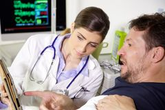 Doctor showing results of test on tablet to worried patient in hospital stock photography