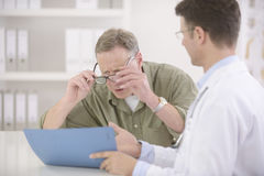 Doctor showing results to myopic patient. Doctor showing results to myopic or bewildered patient at office Stock Image