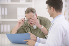 Doctor showing results to myopic patient. Doctor showing results to myopic or bewildered patient at office Royalty Free Stock Photo