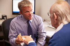 Doctor Showing Senior Male Patient Model Of Human Ear stock photos