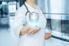 A doctor is showing a shield with medical symbol inside. A young doctor is holding a shield with medical symbol ine at the blurred hospital hall background. The stock photo