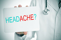 Doctor showing a signboard with the question headache? Royalty Free Stock Photography