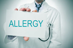 Doctor showing a signboard with the word allergy Stock Photography