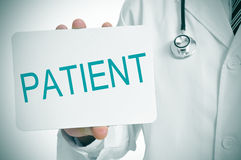 Doctor showing a signboard with the word patient written in it Royalty Free Stock Photo
