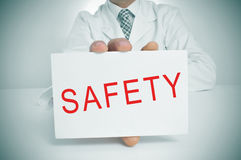 Doctor showing a signboard with the word safety Royalty Free Stock Photography