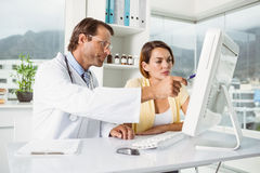 Doctor showing something on computer screen to patient Royalty Free Stock Photography