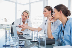 Doctor showing something on a laptop to her colleagues. During a meeting room stock images