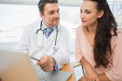 Doctor showing something on laptop to patient in medical office Royalty Free Stock Photo