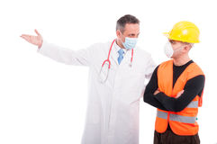 Doctor showing something to constructor. Wearing marks and protection helmet isolated on white background with copy text space Royalty Free Stock Photography