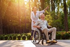 Doctor show something interest to old man in wheelchair. Doctor is showing something to the old men in wheelchair in summer park Stock Photo