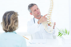 Doctor showing spine model to his patient Stock Photography