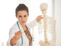 Doctor showing on spine and pointing in camera Stock Photos
