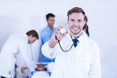 Doctor showing stethoscope towards camera. And other doctor examining a patient behind in hospital Royalty Free Stock Photography