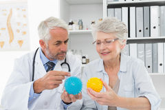 Doctor showing stress buster balls to senior patient Royalty Free Stock Image