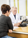 Doctor Showing Tablet Computer To Female Patient. Mature doctor showing tablet computer to female patient in clinic royalty free stock image