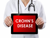 Doctor showing tablet with CROHN'S DISEASE text Stock Photos