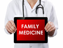 Doctor showing tablet with FAMILY MEDICINE text. Royalty Free Stock Photos