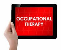 Doctor showing tablet with OCCUPATIONAL THERAPY text. Stock Photos
