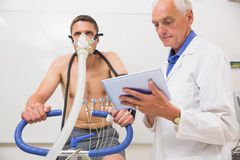 Doctor showing tablet pc to man doing fitness test Stock Photography