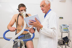 Doctor showing tablet pc to man doing fitness test Royalty Free Stock Images