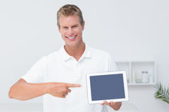 Doctor showing tablet pc. Doctor using tablet pc in medical office Royalty Free Stock Photography