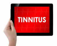 Doctor showing tablet with TINNITUS text. Stock Photos