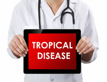 Doctor showing tablet with TROPICAL DISEASE text. Royalty Free Stock Photography