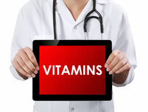 Doctor showing tablet with VITAMINS text. Royalty Free Stock Images
